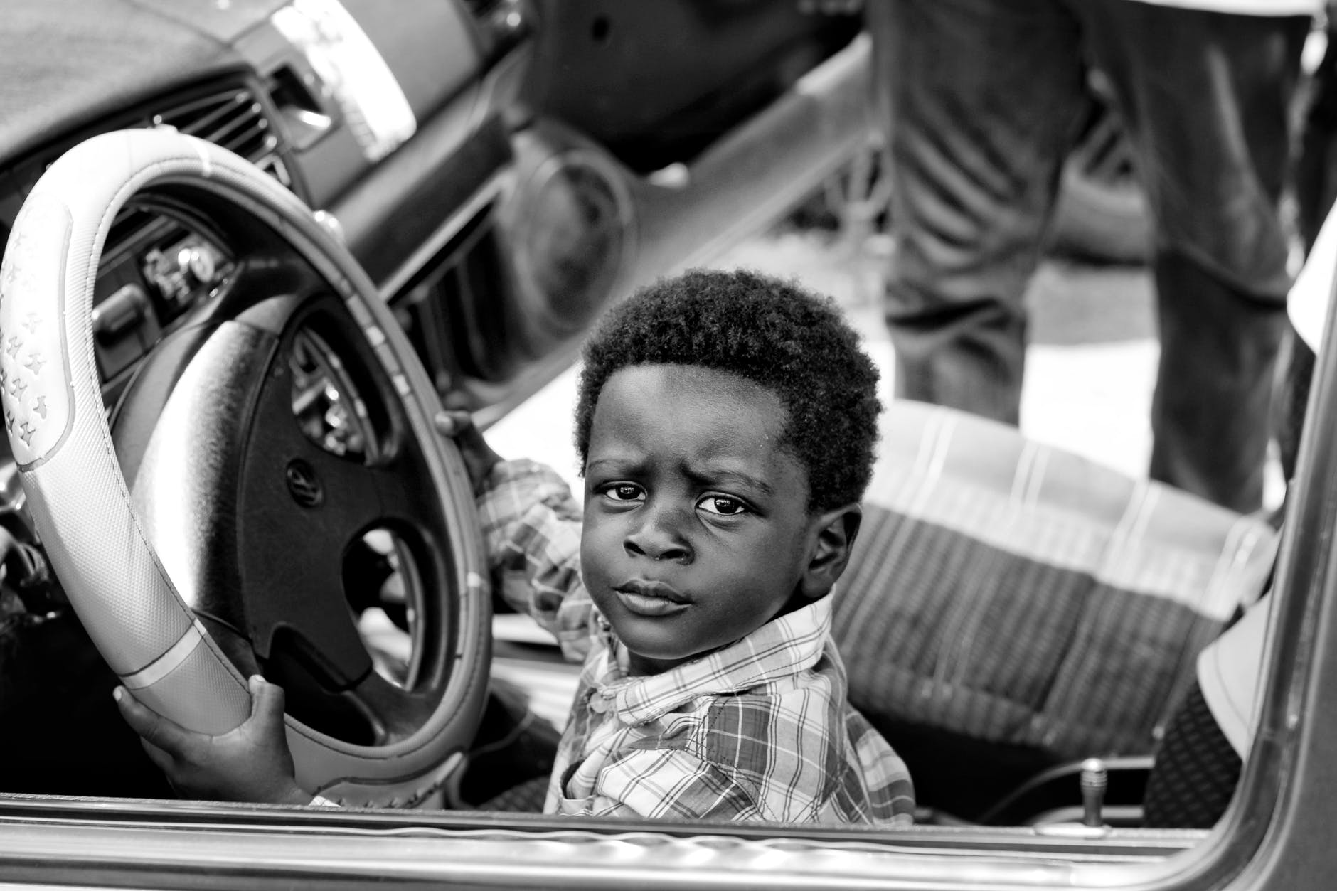 grayscale photo of boy riding car